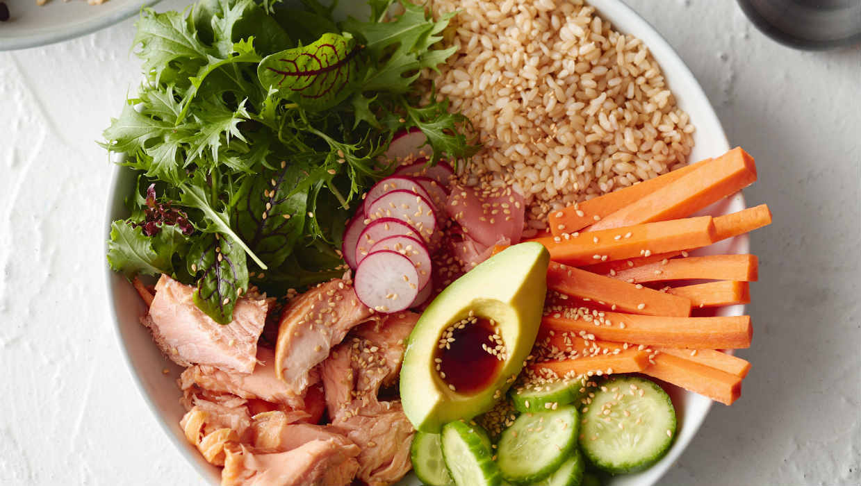 Hot smoked salmon poke bowl with vegetables and brown rice
