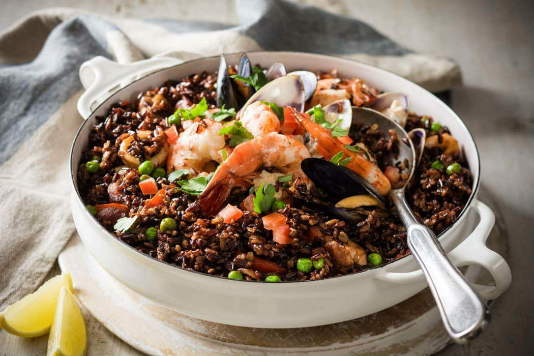 Spanish paella with black rice and seafood
